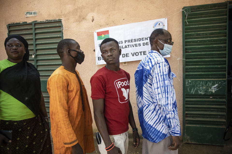 People line up to vote in Burkina Faso's presidential and legislative elections as polling stations open in Ouagadougou, Sunday, Nov. 22, 2020. Voters went to the polls Sunday in Burkina Faso for presidential and legislative elections that have been marred by ongoing extremist violence in this landlocked West African nation. President Roch Marc Christian Kabore has promised to secure the country and is vying for another five years against 12 other candidates. Kabore is expected to win, but the opposition hopes to take the vote to a second round. (AP Photo/Sophie Garcia)