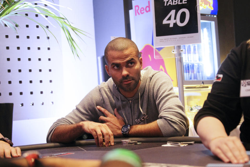 French basketball star Tony Parker (C) sits at a table games on October 18, 2011 in Cannes, to attend his first poker tournament in France.  AFP PHOTO VALERY HACHE (Photo credit should read VALERY HACHE/AFP via Getty Images)