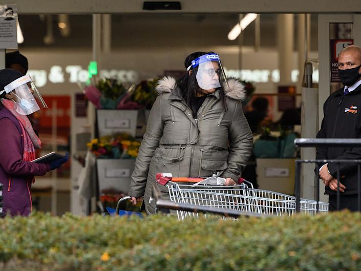 A security guard assists a member of the store team as they stand at the entrance to a branch of Sainsbury's following the company's decision to enforce the mandatory wearing of face masksGetty