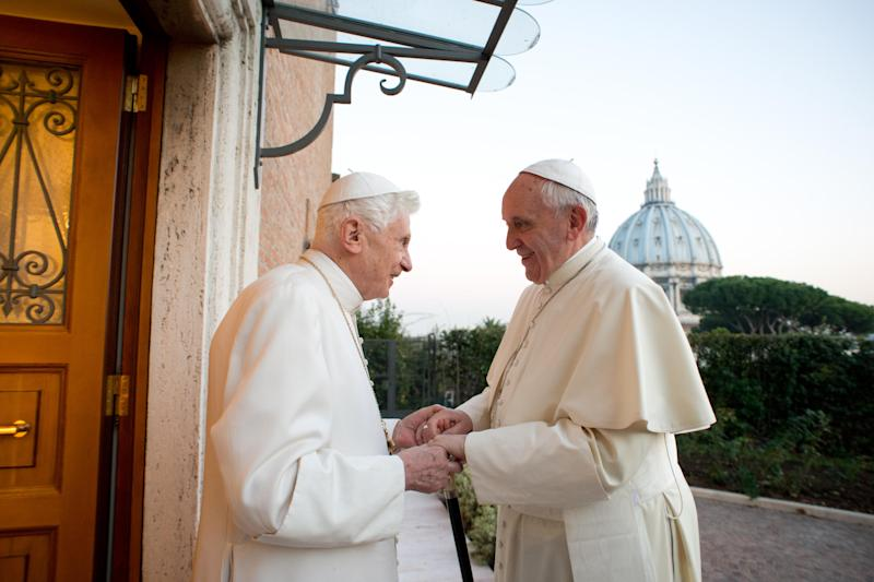 "In this file picture provided by the Vatican newspaper L'Osservatore Romano on Dec. 23, 2013, Pope Emeritus Benedict XVI, left, welcomes Pope Francis as they exchanged Christmas greetings, at the Vatican. It was a holiday at the Vatican and Pope Benedict XVI was speaking in Latin at an arguably boring ceremony announcing new saints, so few people were paying much attention. But what Benedict said a year ago Tuesday changed the course of the 2,000-year-old Catholic Church and paved the way for the historic papacy of Pope Francis. In his soft voice and in a Latin that the cardinals present strained to understand, Benedict announced that he no longer had the ""strength of mind and body"" to be pope and would retire at the end of the month, the first pope to step down in more than half a millennium. (AP Photo/L'Osservatore Romano, ho)"