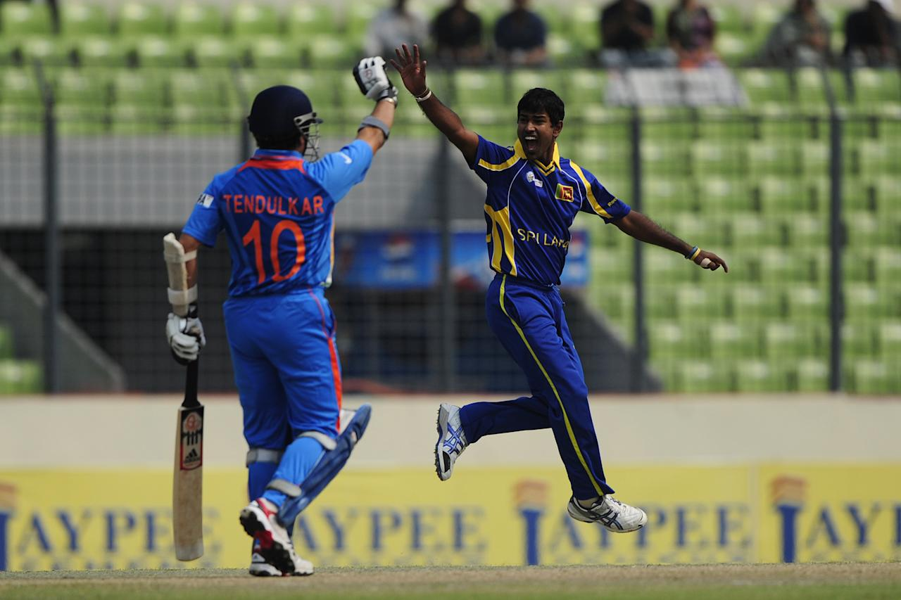 Sri Lankan bowler Nuwan Kulasekara (R) appeals unsuccessfully for a Leg Before Wicket decision as the Indian batsman Sachin Tendulkar reacts during the one day international (ODI) Asia Cup cricket match between India and Sri Lanka at The Sher-e-Bangla National Cricket Stadium in Dhaka on March 13, 2012.