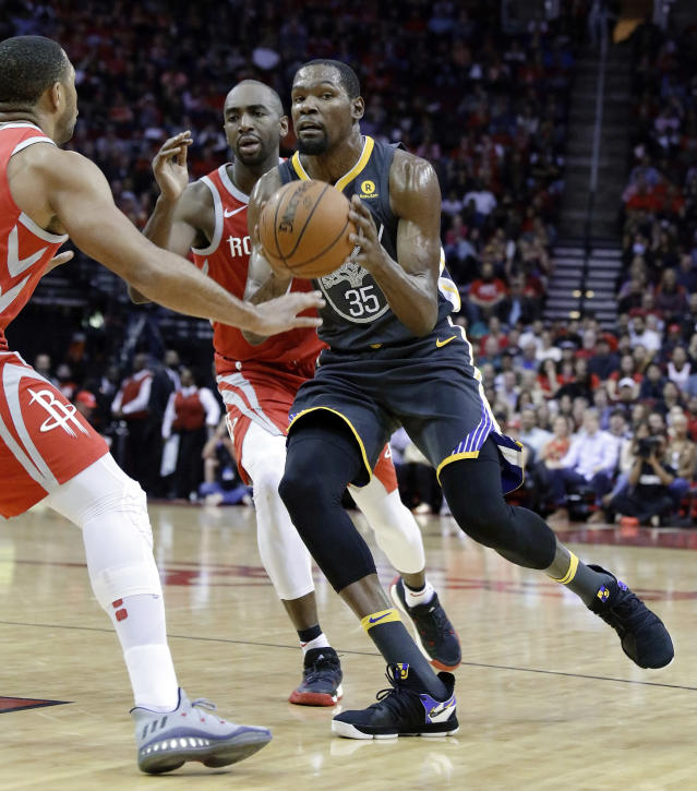 Golden State Warriors forward Kevin Durant (35) looks to pass the ball between Houston Rockets guard Eric Gordon (10) and forward Luc Mbah a Moute (12) during the first half of an NBA basketball game Saturday, Jan. 20, 2018, in Houston. (AP Photo/Michael Wyke)