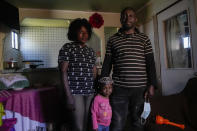 Married Haitian couple Pierre and Benita and their three-year-old, Chilean-born daughter Benita pose for a portrait inside their home in Santiago's Dignidad camp set up by migrants in Chile, Thursday, Sept. 30, 2021. Pierre, 37, says he feels caught in a vicious circle: he is unemployed and cannot get a job without a valid identity card, but he can't get his card renewed without an employment contract. (AP Photo/Esteban Felix)
