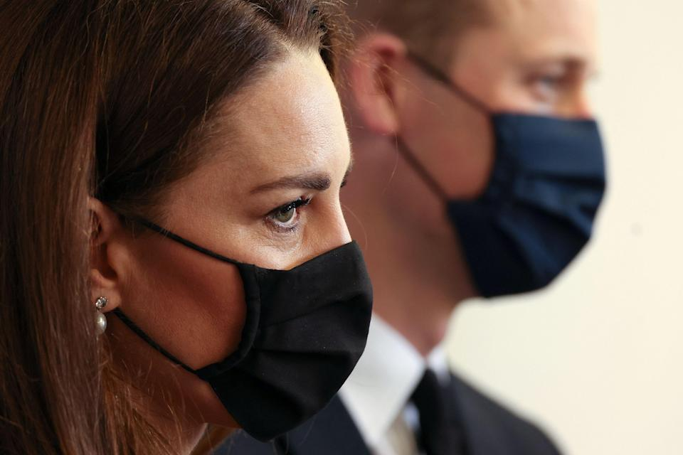 Prince William and Duchess Kate, wearing black following the death of Prince Philip, talk with Air Cadets during a visit to a training base in East London on April 21, 2021.