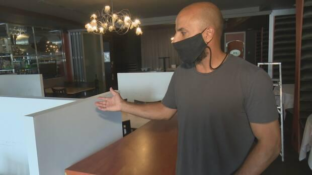 Mezzo Ristorante and Lounge owner Filip Rocca shows barriers put between tables in preparation for indoor dining. (Dale Molnar/CBC - image credit)