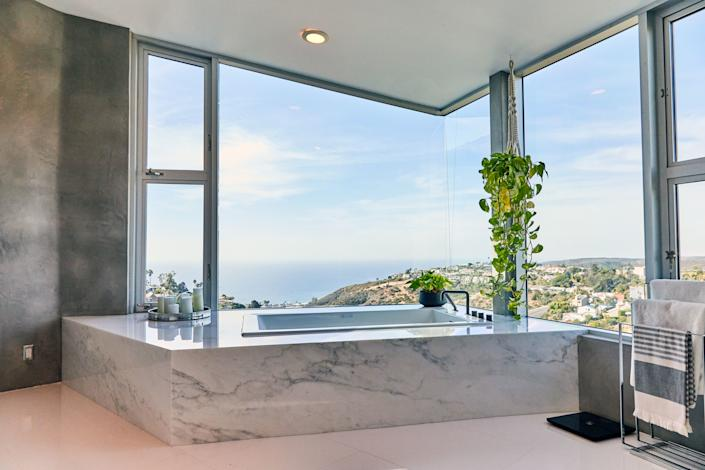"A friend connected Huston with a marble company in Los Angeles, where he chose the pieces fitted around his massive tub, which he does soak in from time to time. ""I love the way it turned out, the modern look of it,"" he says. ""And the plants there, too, help out with the good vibe."""