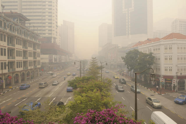 A main street in Singapore's Chinatown is covered with a thick haze on Friday, June 21, 2013. Air pollution in Singapore has soared to record heights for a third consecutive day, as Indonesia prepared planes and helicopters to battle raging fires blamed for hazardous levels of smoky haze in three countries. (AP Photo/Joseph Nair)