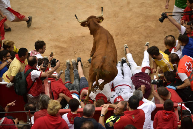 <p>A cow jumps over men laid on the ground following the running of the bulls at the San Fermin Festival, in Pamplona, northern Spain, July 14, 2017. (Photo: Alvaro Barrientos/AP) </p>