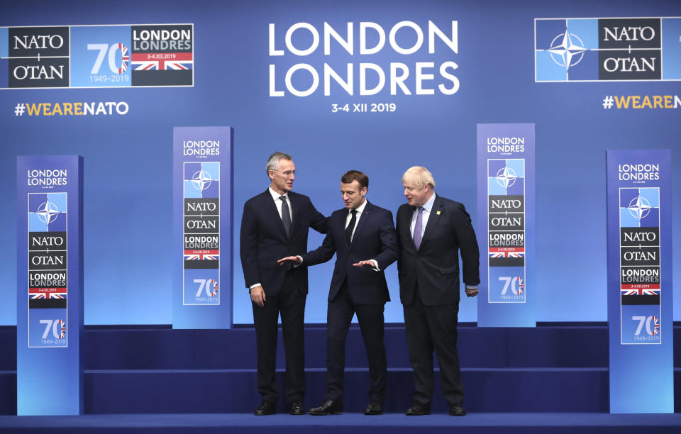 NATO Secretary General Jens Stoltenberg, left, and British Prime Minister Boris Johnson, right, welcome French President Emmanuel Macron at official arrivals for a NATO leaders meeting at The Grove hotel and resort in Watford, Hertfordshire, England, Wednesday, Dec. 4, 2019. NATO Secretary-General Jens Stoltenberg rejected Wednesday French criticism that the military alliance is suffering from brain death, and insisted that the organization is adapting to modern challenges. (AP Photo/Francisco Seco)