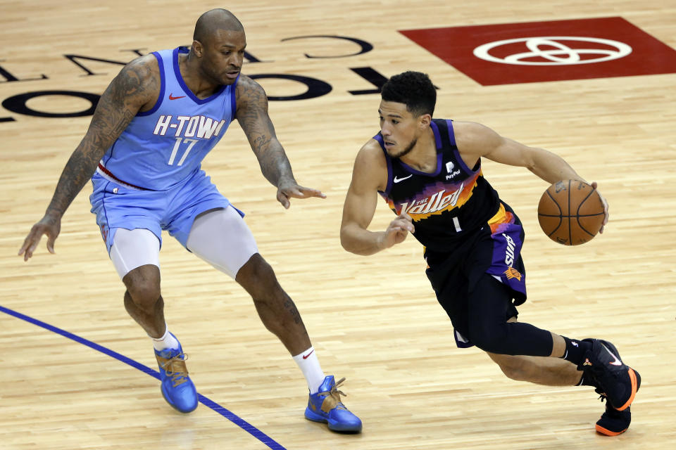 Phoenix Suns guard Devin Booker (1) drives around Houston Rockets forward P.J. Tucker (17) during the second half of an NBA basketball game Wednesday, Jan. 20, 2021, in Houston. (AP Photo/Michael Wyke)