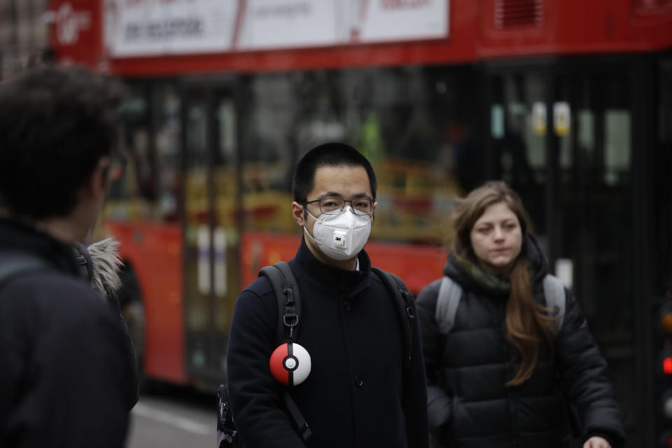 A man wearing a face mask walks backdropped by a red London bus across the street from the Bank of England in London, Wednesday, March 4, 2020. British authorities laid out plans Tuesday to confront a COVID-19 epidemic, saying that the new coronavirus could spread within weeks from a few dozen confirmed cases to millions of infections, with thousands of people in the U.K. at risk of death. (AP Photo/Matt Dunham)