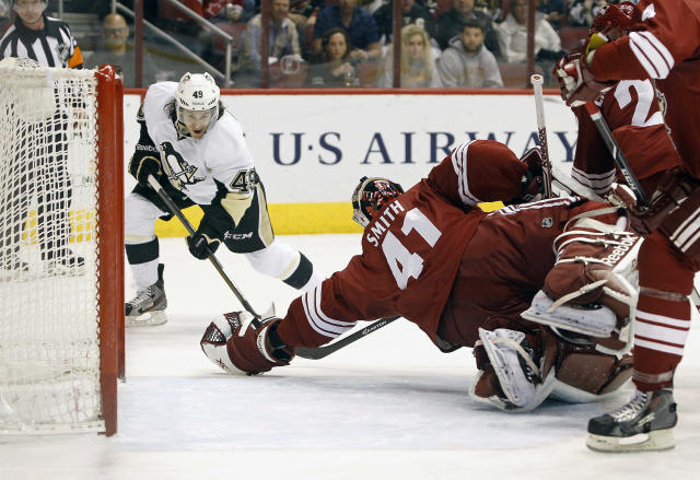 Phoenix Coyotes goaltender Mike Smith (41) makes a diving glove save on the shot by Pittsburgh Penguins' Brian Gibbons (49) during the first period of an NHL hockey game on Saturday, Feb. 1, 2014, in Glendale, Ariz. (AP Photo/Ralph Freso)