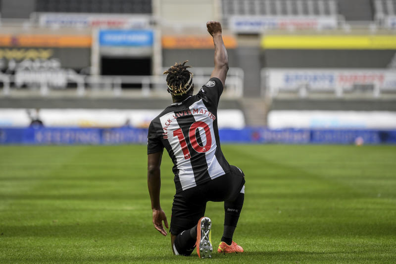 Newcastle's Allan Saint-Maximin takes a knee as he celebrates his goal during the English Premier League soccer match between Newcastle United and Sheffield United at St James' Park stadium in NewCastle, England, Sunday, June 21, 2020. (Michael Regan/Pool via AP)