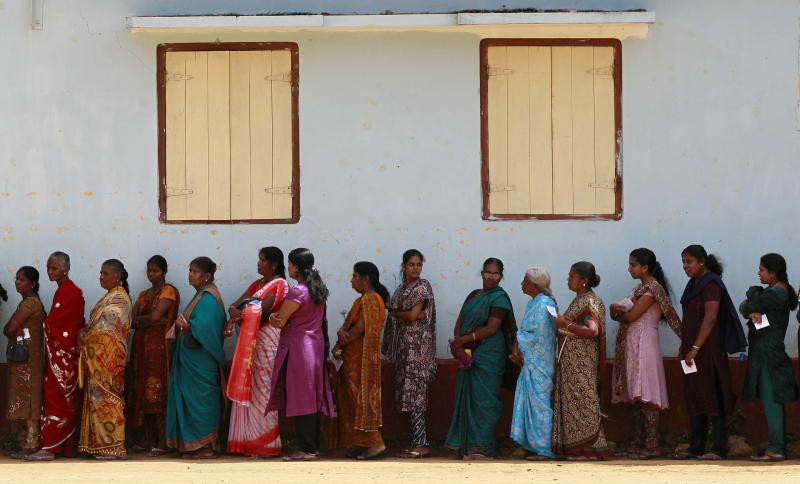 Sri Lankan ethnic Tamil women wait to cast their votes at a polling station during the northern provincial council election in Jaffna, Sri Lanka, Saturday, Sept. 21, 2013. The voters in Sri Lanka's war-ravaged north went to the polls Saturday to form their first functioning provincial government, hoping it is the first step toward wider regional autonomy after decades of peaceful struggle and a bloody civil war. (AP Photo/Eranga Jayawardena)