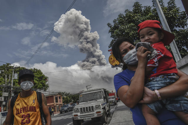 <p>A woman covers the face of a child as Mount Mayon spews a huge column of ash noon in Camalig, Albay province, Philippines, Jan. 24, 2018. (Photo: Ezra Acayan/NurPhoto via Getty Images) </p>