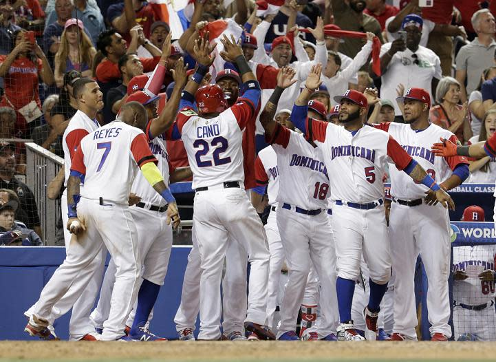 Dominican Republic's Robinson Cano (22) is met by his teammates after scoring on a single by Carlos Santana. (AP)