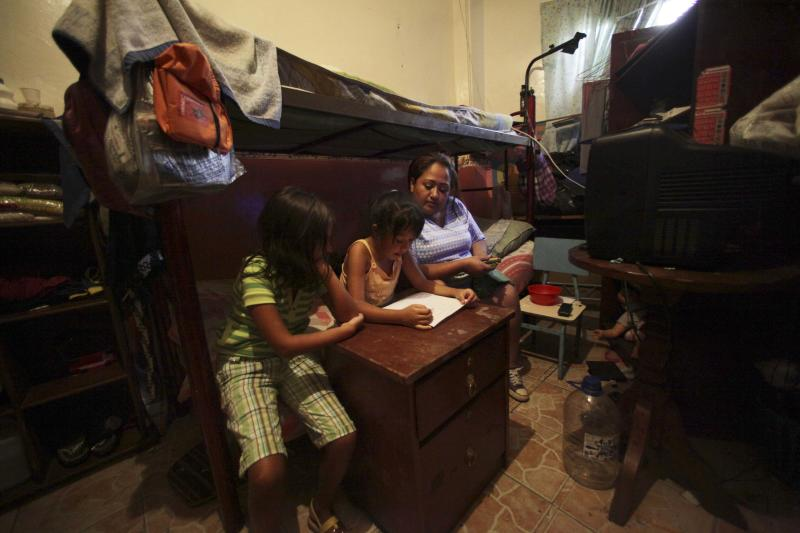 In this Sept. 27, 2012 photo, Maribel Rodriguez, right, sits with her daughters as they do their homework in the room where they live that was once a school but is now a government provided shelter for families who have lost their homes due to flooding, in Caracas, Venezuela. Fear of every stripe, like the loss of government housing like this one, permeates the intensely polarized election campaign, with many votes to be decided based not on the candidates' promises but rather on what worries people most. Chavez has continuously warning of chaos and the dismantling of the generous welfare state he built if he is voted out of office in the Oct. 7 vote. (AP Photo/Fernando Llano)
