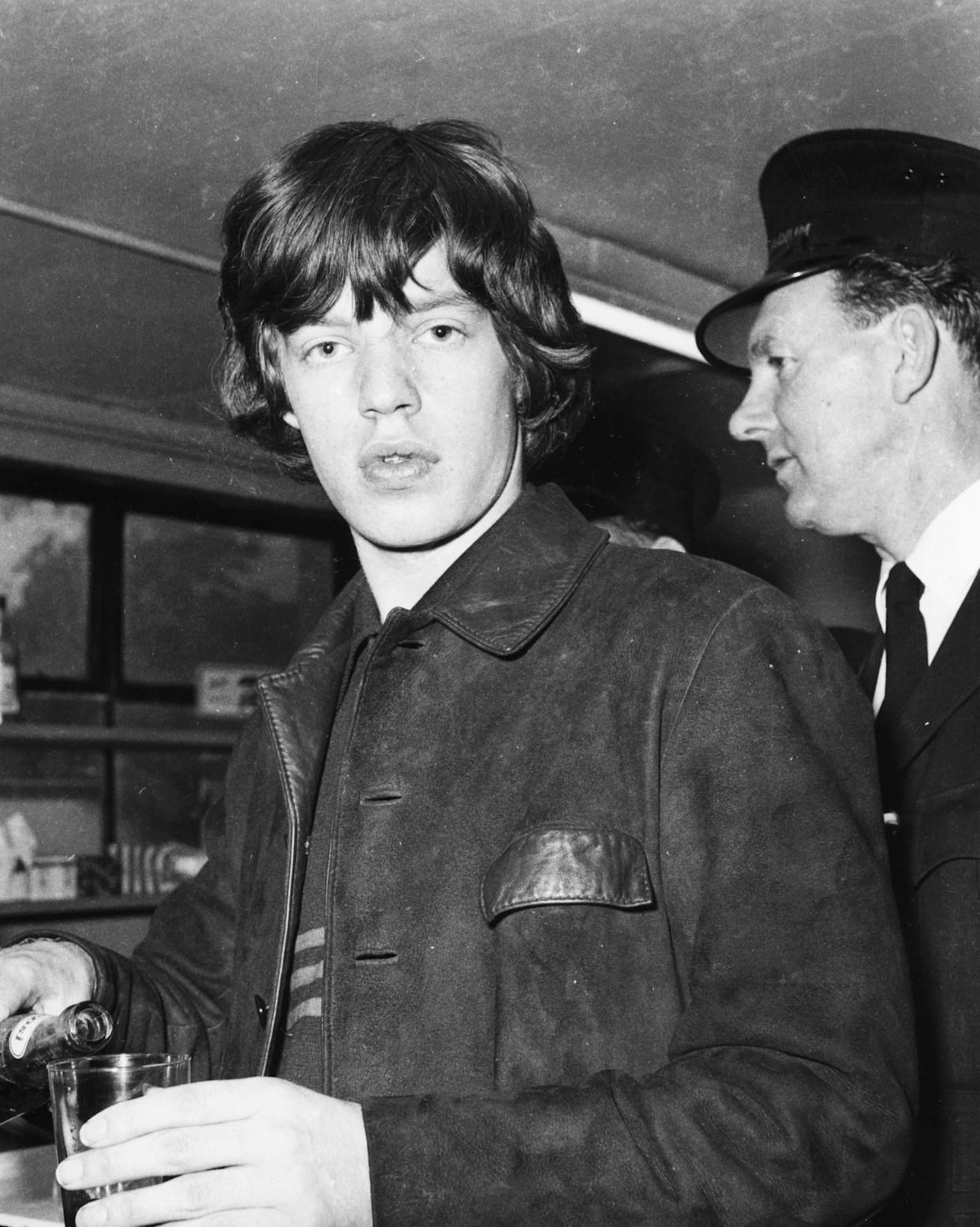 'The Rolling Stones' lead singer Mick Jagger pouring himself a drink, 1964. (Photo by Keystone Features/Hulton Archive/Getty Images)