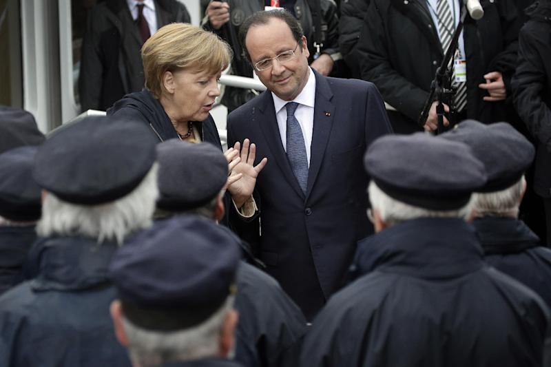German Chancellor Angela Merkel, left, and President of France Francois Hollande, right, talk as they listen to a shanty choir during a joint visit on the Baltic see island Ruegen, northern Germany, Friday, May 9, 2014. Merkel and Hollande meet for two days on the island Ruegen and in the coastal city of Stralsund. (AP Photo/Michael Sohn)