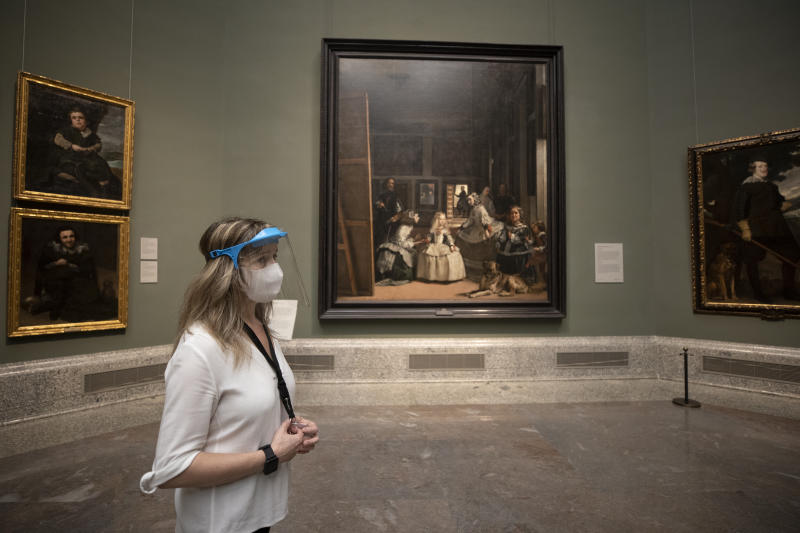 A staff member of the museum stands in front of 'Las Meninas' by Diego de Velazquez before the reopening on June 6 amid the coronavirus disease (COVID-19) outbreak at El Prado museum in Madrid, Spain, Thursday, June 4, 2020. Three of Madrid's most famous museums are set to reopen on June 6 as Spain winds down its restrictions on movement due to the new coronavirus. (AP Photo/Manu Fernandez)