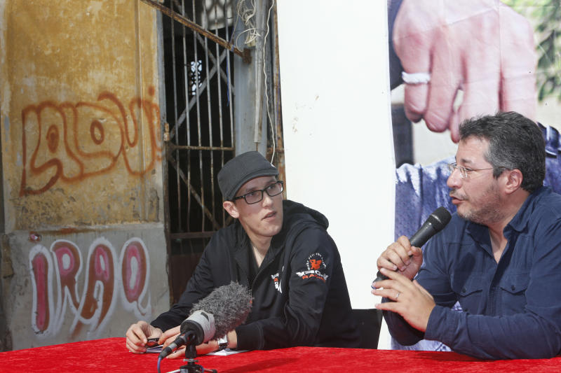 """Mouad Belghouat known as el-Haqed or """"the Enraged,"""" left and Abdellah Abaakil, an activist with the February 20 movement who introduced the rapper at the press conference, as he speaks to the media at the old slaughterhouse in Casablanca, Friday March 29, 2013. The Moroccan rapper, known for his social activism and protest songs, said he will concentrate on his music and studies after being released from prison for insulting police. (AP Photo/Abdeljalil Bounhar)"""