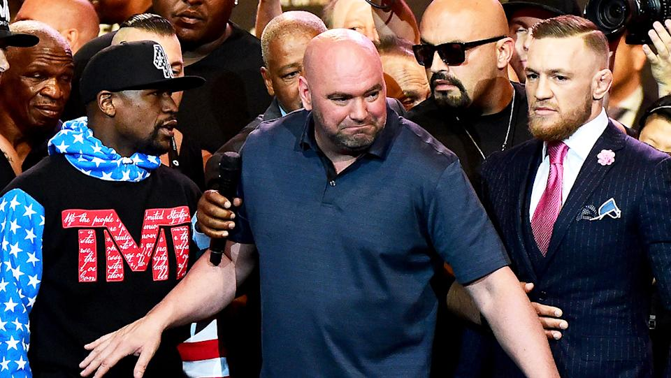 UFC boss Dana White (pictured middle) holding back Floyd Mayweather (pictured left) and Conor McGregor (pictured right).