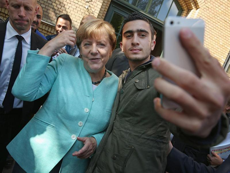 A photo of Anas Modamani taking a selfie with Angela Merkel went viral after it was used by news organisations around the world (Getty)