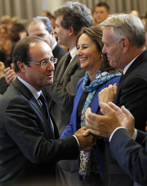 French President-elect Francois Hollande, left, shakes hands with President of the Socialist group at the National Assembly Jean-Marc Ayrault during the Socialist Party's national council, in Paris, Monday, May 14, 2012. Former French Socialist presidential candidate Segolene Royal, center right, looks on. (AP Photo/Christophe Ena)