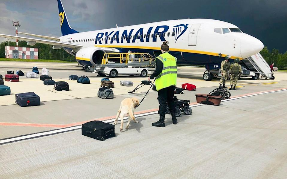 A security guard checks the luggage of passengers on the 'hijacked' Ryanair plane in Minsk - AP