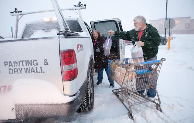 Dave and Debbie Teed load their shopping bags into their vehicle at the Walmart parking lot near the North Belt Highway in St. Joseph, Mo., Tuesday, Feb. 4, 2014. A winter storm bore down on Missouri Tuesday, dumping enough snow to make roads treacherous and forcing the cancellation of dozens of flights and hundreds of schools. (AP Photo/The St. Joseph News-Press, Sait Serkan Gurbuz)