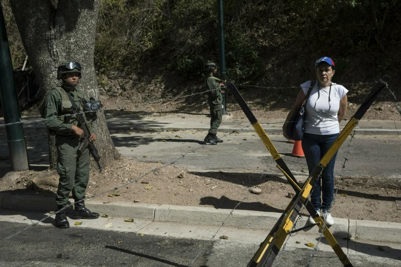 A woman stands next to soldiers as other members of the opposition hand out copies of an amnesty law near Ft. Tiuna military base in Caracas, Venezuela, Sunday, Jan. 27, 2019. Opposition National Assembly leader Juan Guaido, who declared himself interim president, said Friday that he would release the text of an existing amnesty law that would pardon members of the military who cooperate in restoring democracy and asked Venezuelans to share it with officers they know. (AP Photo/Rodrigo Abd)