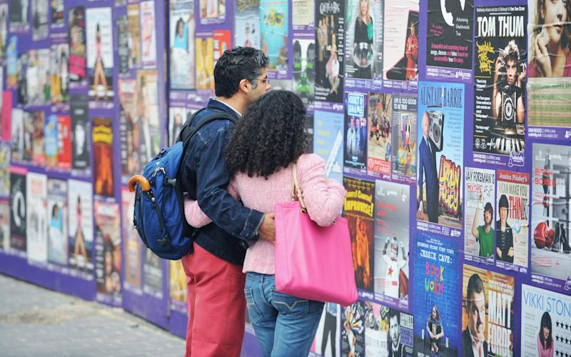 A couple look at show posters in Bristo Square at the Edinburgh Festival Fringe - Getty Images Europe
