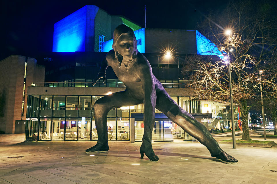 The 'Messenger' sculpture depicting a female actor ready to run on stage and skyline of Plymouth illuminated at night in South Devon outside of Theatre Royal. The sculpture was created by Cornish sculptor Joseph Hillier and unveiled in 2019