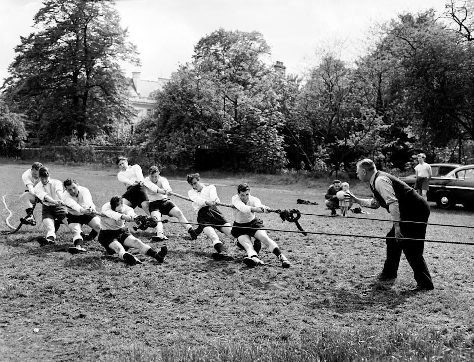 The team splits into two halves to pull against each other with a rope over a pulley, under the eye of their coach, Sergeant George Hutton.