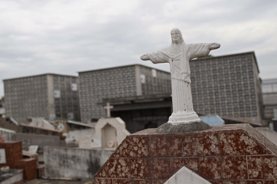 A small version of the Christ the Redeemer statue stands in front of niches at the Iraja cemetery, where many COVID-19 victims are buried in Rio de Janeiro, Brazil, Friday, Feb. 5, 2021. (AP Photo/Silvia Izquierdo)