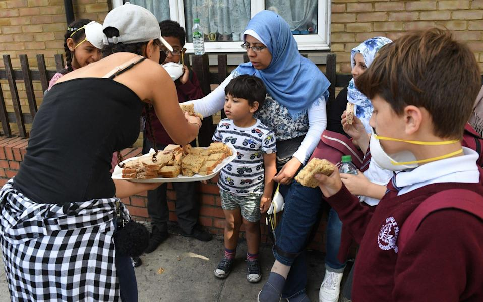 Sandwiches are handed out to local residents close to a fire that has engulfed the 24-storey Grenfell Tower in west London - Credit: Victoria Jones/PA