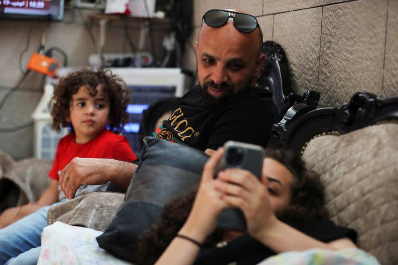 Mohammed, father of Jana Kiswani, sits next to his daughter as she rests at home after she was injured in the Sheikh Jarrah neighbourhood of East Jerusalem
