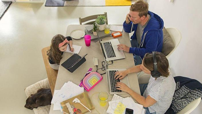 A family working from home sit around a dining table on laptops