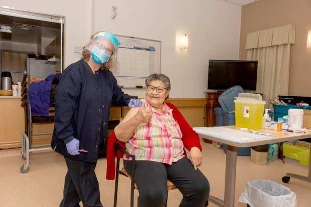 Caroline Douglas, a resident of the Jimmy Erasmus Seniors Home in Behchokǫ̀, gives the thumbs up sign after receiving the Moderna COVID-19 vaccine.