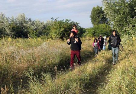 Migrants from Afghanistan walk just after they crossed the border from Serbia to Hungary, near the village of Asotthalom, Hungary, on June 29, 2015. REUTERS/Laszlo Balogh