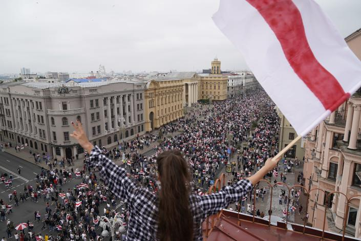 FILE - In this Aug. 23, 2020, file photo, a woman waves an old Belarusian national flag standing on the roof as Belarusian opposition supporters march to Independence Square in Minsk, Belarus. The diversion of a Ryanair flight to Lithuania by Belarus, leading to the arrest of Raman Pratasevich, an opposition journalist who was a passenger, has sparked international outrage and calls for tough sanctions against the former Soviet nation. Pratasevich ran a popular messaging app that helped organize the demonstrations. (AP Photo/Evgeniy Maloletka, File)