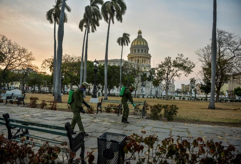 Cuban soldiers disinfect a square in Havana that has been left virtually deserted due to the coronavirus outbreak (AFP Photo/YAMIL LAGE)