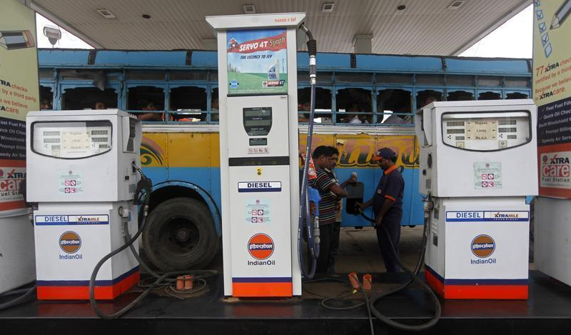An employee fills diesel in a public bus at a fuel station in Kolkata