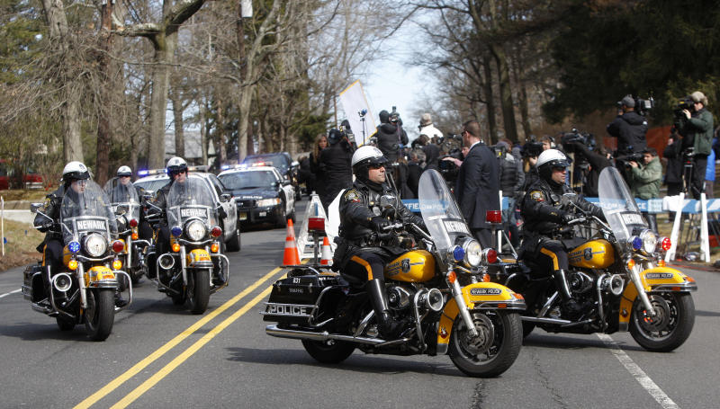 A Newark Police Department motorcade escorts the hearse carrying the body of Whitney Houston arrives at Fairview Cemetery for her burial in Westfield, N.J., Sunday, Feb. 19, 2012. (AP Photo/Rich Schultz)