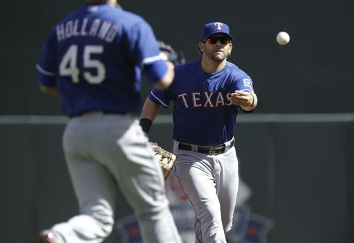Texas Rangers' Mitch Moreland, right, tosses the ball to pitcher Derek Holland who races to the bag for the out after Minnesota Twins' Joe Mauer grounded to Moreland in the first inning of a baseball game on Saturday, April 27, 2013, in Minneapolis. (AP Photo/Jim Mone)