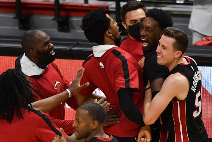 Apr 18, 2021; Miami, Florida, USA; Miami Heat center Bam Adebayo (top right) celebrates a winning shot over the Brooklyn Nets with teammates at American Airlines Arena. Mandatory Credit: Jim Rassol-USA TODAY Sports