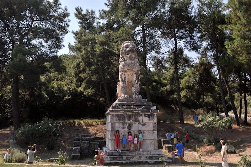 Tourists take photos of a marble Lion statue on August 16, 2014 near the site where archaeologists have unearthed a funeral mound dating from the time of Alexander the Great, in Amphipolis, northern Greece (AFP Photo/Sakis Mitrolidis)