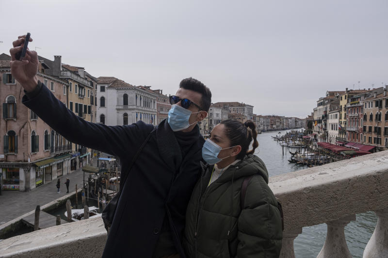 VENICE, ITALY - MARCH 06: Tourists with protective face masks take a selfie on the Rialto Bridge on March 06, 2020 in Venice, Italy. Venice is deserted because of COVID-19, yesterday, March 5, a third person died in the city due to the COVID-19 virus. The latest Civil Protection bulletin talks about 3,858 COVID-19 positives, 148 people died and 414 have recovered in Italy. (Photo by Stefano Mazzola/Awakening/Getty Images)