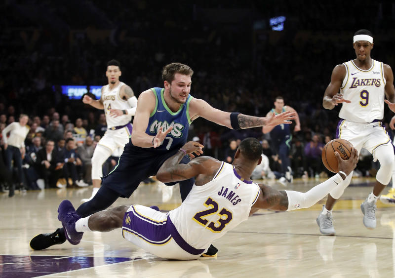 Los Angeles Lakers' LeBron James (23) recovers a loose ball under Dallas Mavericks' Luka Doncic (77) during the first half of an NBA basketball game Sunday, Dec. 1, 2019, in Los Angeles. (AP Photo/Marcio Jose Sanchez)