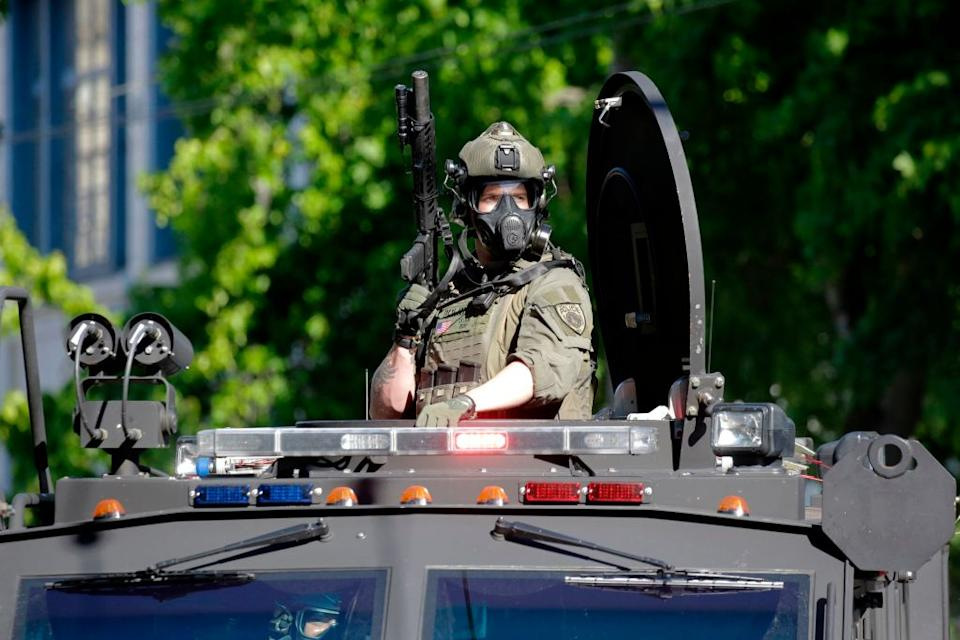 A Seattle SWAT officer rides on an armored vehicle as police and protesters clash on the weekend. Source:  Getty